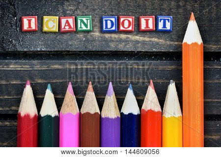 I can do it text and group of pencil on wooden table