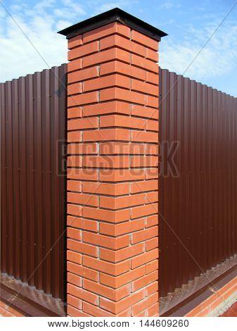 Brick pillar metal fence around a country house