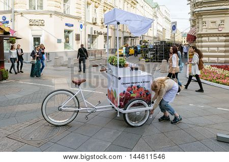 Moscow, Russia - July 07, 2016: Girl sets the counter with a refrigerator attached to the bike for sale of fresh fruits and berries
