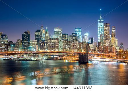 Aerial view of  Brooklyn Bridge and Lower Manhattan skyline in New York City at night with city illumination, USA
