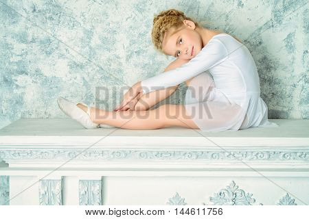 Beautiful romantic little ballet dancer sitting on a fireplace. Vintage style.