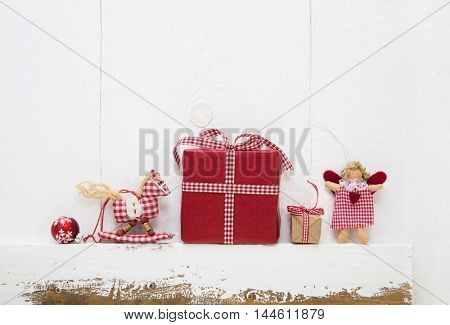Red white checked christmas presents with horse and angel on wooden old shabby background for decoration.