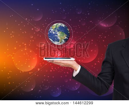 Businessman hands holding tablet with Earth planet on abstract background. Elements of this image are furnished by NASA