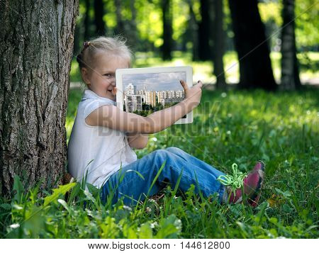 Little girl Little girl on the grass with tablet. Happy kid shows photos of the city on the tableton the grass with tablet. Happy kid shows photos of the city on the tablet