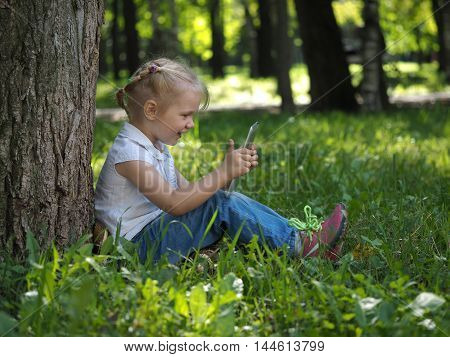 Child with tablet pc outdoors. Little girl on the grass with a computer