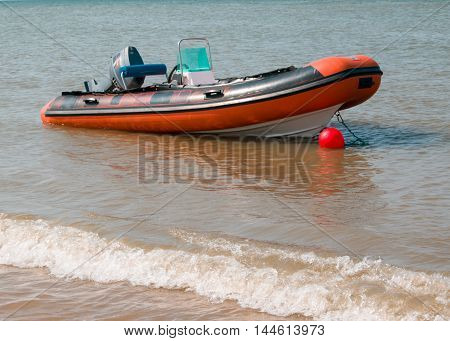 Beautiful red inflatable boat on coast of beach, blurred selective focus.