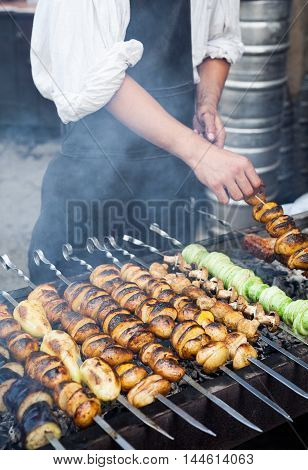Grilled vegetables barbecue skewers healthy meal picnic food shish kebab with roasted pepper, potatoes, champignon, on coal ember brazier. Concept of lifestyle rustic street food preparation
