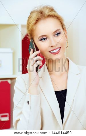 Pleasant business woman talking on the phone at the office and smiling.