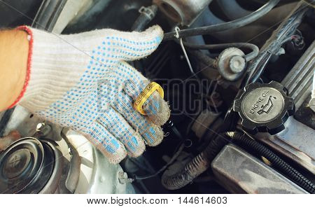The oil dipstick of the car in a hand