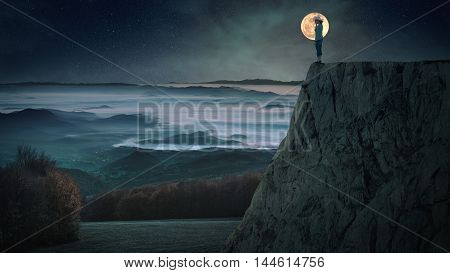 Lonely woman standing on the edge of a cliff on the night of the full moon with a view of valley covered with fog.