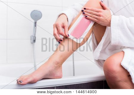 Woman sitting at edge of tub in bathroom using wax strips for depilation