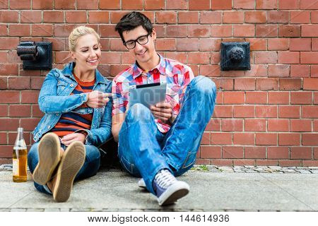 Hipster tourists, woman and man, planning their Berlin vacation with a pad computer sitting in front of brickwall