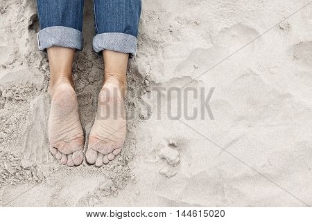 Relaxed sandy young woman feet on the beach. Plenty of copy space on the right