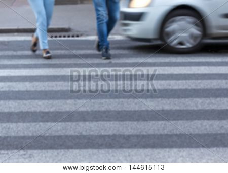 Busy city street with people and car in motion blur on crosswalk. Dangerous scene with disregard of traffic regulations. Speed concept.
