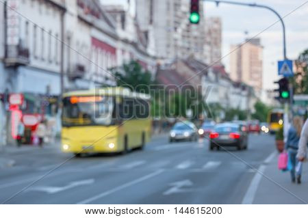 Busy city street with yellow bus people and cars in motion blur. Traffic light regulation.