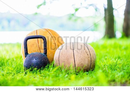 Training equipment in the grass - ball and kettlebell