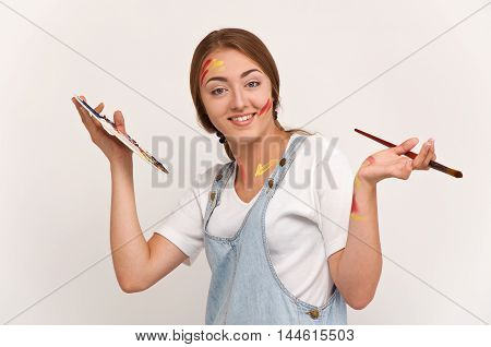 pretty young artist holding a palette and brushes. creation