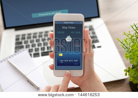 female hand holding white phone with online ship ticket in screen on table with notebook
