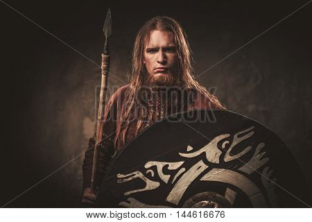 Serious viking with a spear in a traditional warrior clothes on a dark background.