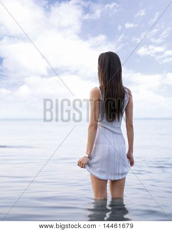 Young sexy lady standing in the warm water