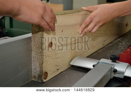 Wooden board is treated by a carpenter on planer
