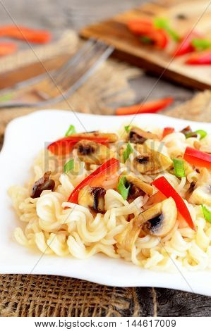 Mushroom pasta with vegetables on a plate. Pasta with roasted mushrooms, red pepper and green onions. Vegetarian recipe. Homemade healthy food. Closeup