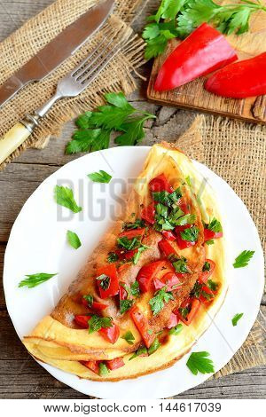 Stuffed egg omelette with vegetables on a plate. Healthy omelet with fried red pepper, fresh parsley and spices. Fork, knife on a burlap and old wood background. Easy eggs recipe. Top view