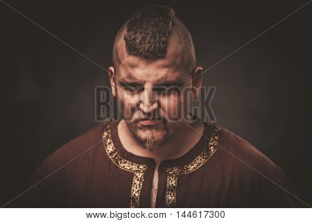 Angry viking in a traditional warrior clothes on a dark background.
