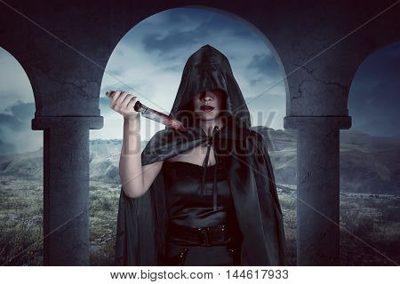 Young Asian Witch Woman Holding Bloodstained