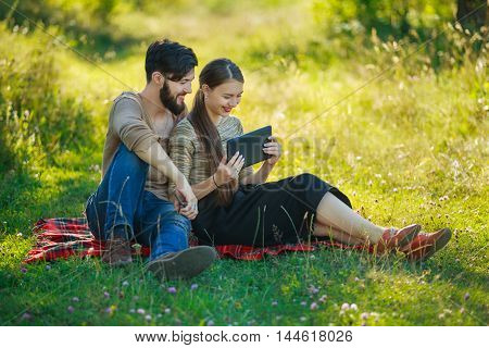 happy couple with a tablet in nature