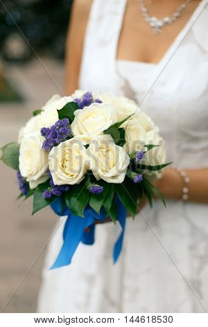 Bride holding round wedding bouquet of cream roses and purple flowers with a blue ribbon