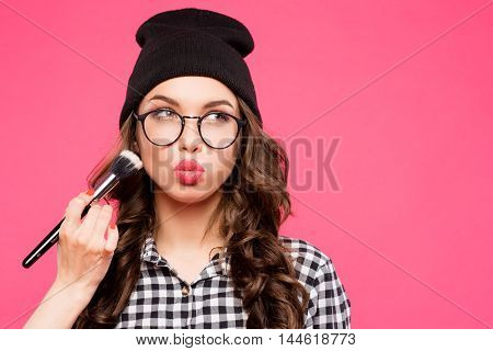 Young hipster girl having fun and going crazy, wearing glasses hat and bright make up. Pink urban background. The woman made his lips in a kiss , make up, make up girl, puffed out his cheeks.