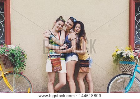 Happy boho chic stylish girls pose with bicycles near house facade. Beautiful women and bicycles with baskets full of wild flowers. Female friends, youth fashion, summer leisure in park concept.