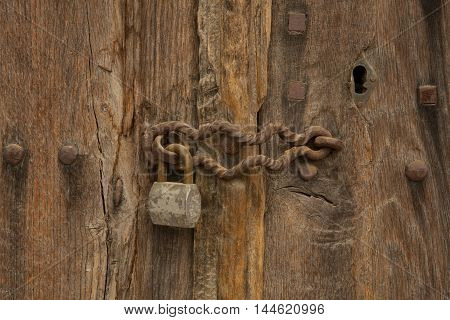 rusty padlock on an old wooden door