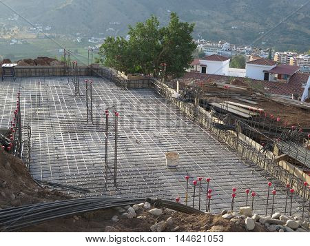 Newly poured concrete floor with steel mesh and poles
