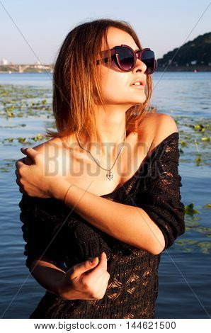 Sexy young woman with short hair tanned skin and bare shoulders wearing sun glasses and black lace dress posing on the beach in summer