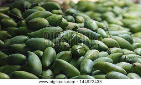 Traditional asian market stall full of fresh green mangoes