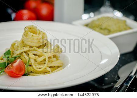 pasta spaghetti with pesto genovese on black background
