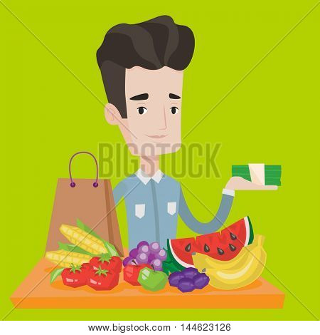 Young man standing at the table with shopping bag, fruits and vegetables on it. Shopper holding stack of money in hand in front of table full of food. Vector flat design illustration. Square layout.