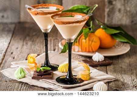 Irish cream liqueur in a glass with   cinnamon on wooden background