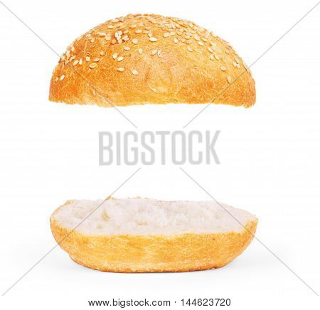Burger bun empty isolated. American food classic burger round bun with sesame isolated at white background. Burger bun without ingridients. Roasted toasted hamburger bun layers flying at white.