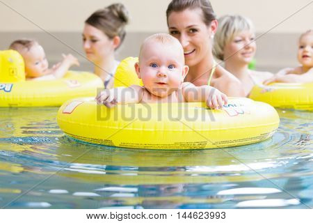 Mums and their children having fun together playing with toys at baby swimming lesson