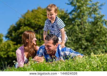 Family lying in grass on meadow, son riding on dad