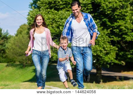 Family running fast in grass on meadow
