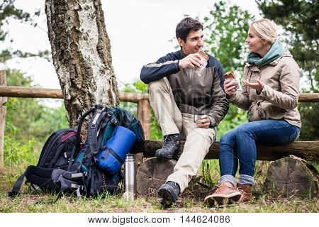 Loving couple, woman and man, on hike taking rest under old birch tree