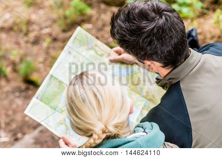 Hikers, man and woman, bending over trail map while resting in the woods