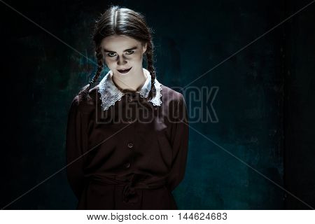 Portrait of a young smiling girl in school uniform as killer woman against school board . The image in the style of Halloween and Addams family