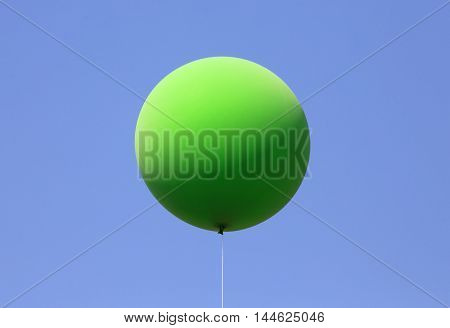 Green balloon on blue cloudless  sky background