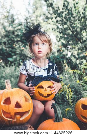 Halloween. Child Dressed In Black With Jack-o-lantern In Hand, Trick Or Treat. Little Girl  Pumpkin