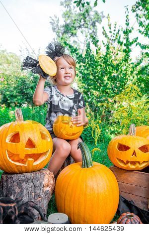 Halloween. Child Dressed In Black With Jack-o-lantern In Hand, Trick Or Treat. Happy Little Girl  Pu
